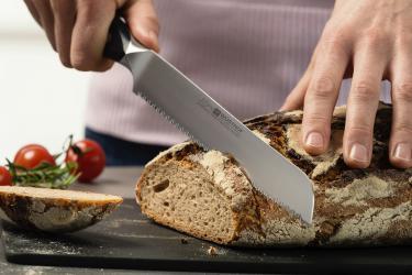 סכין משונן בחיתוך כיכר לחם לפרוסות